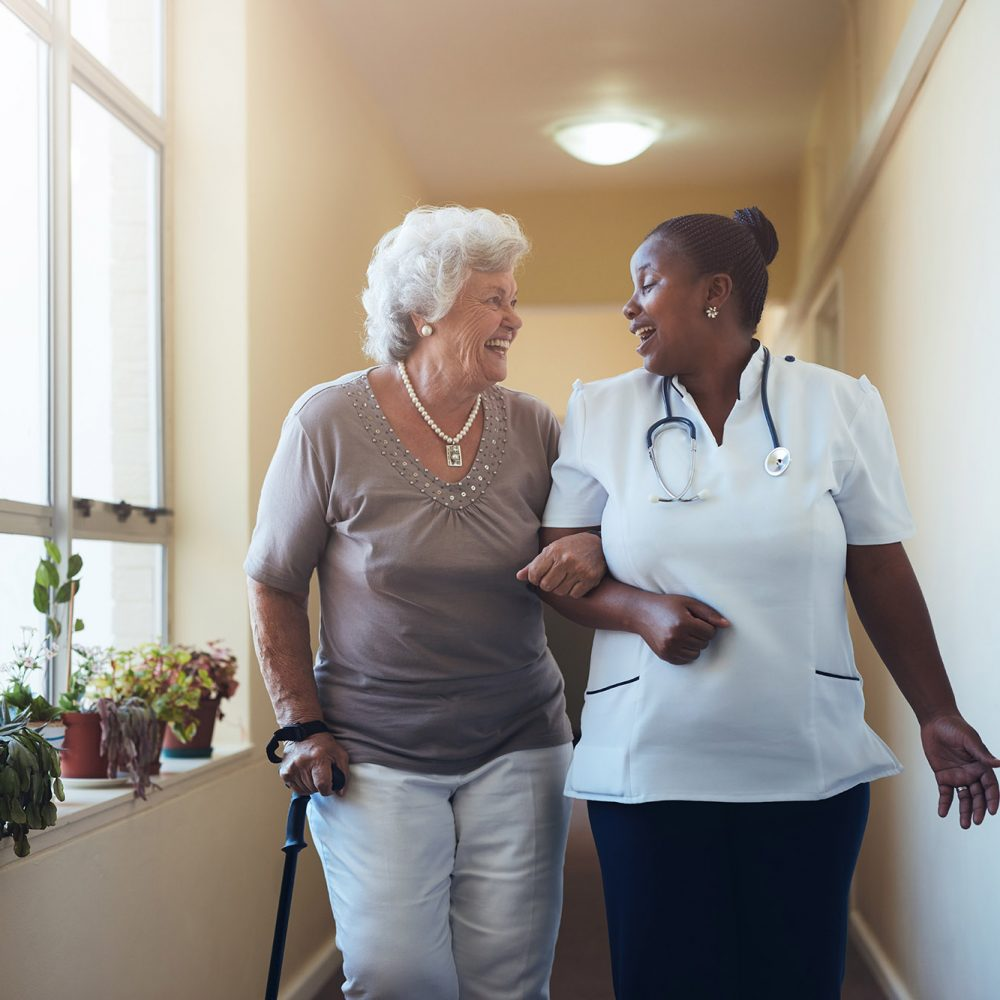 nurse walking down a hallway with an elderly patient