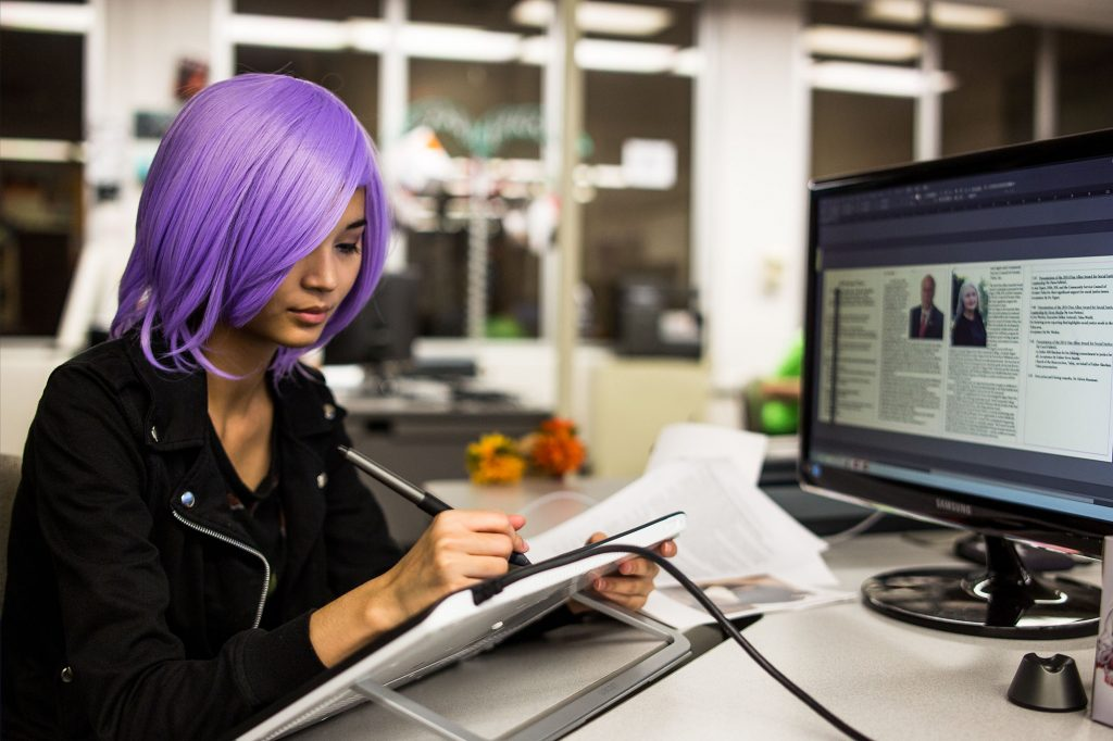 photo of a girl with purple hair drawing on a tablet in graphic design class