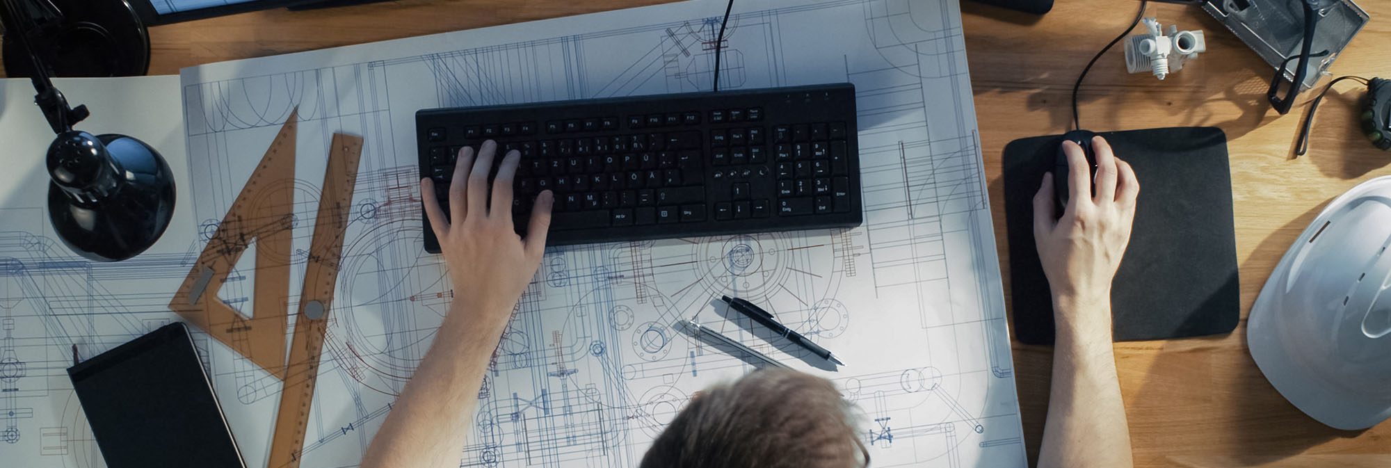 photo of a man working on design drafts at his desk