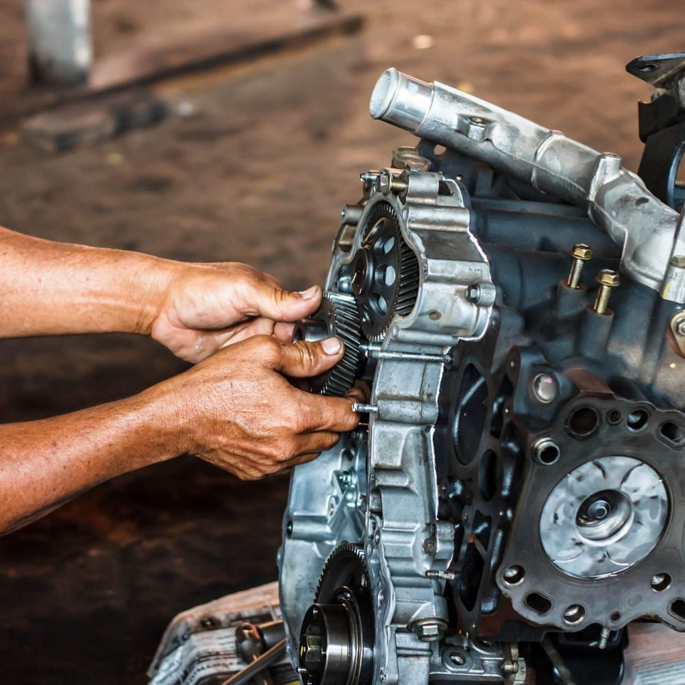 pic of a persons hands repairing a diesel engine