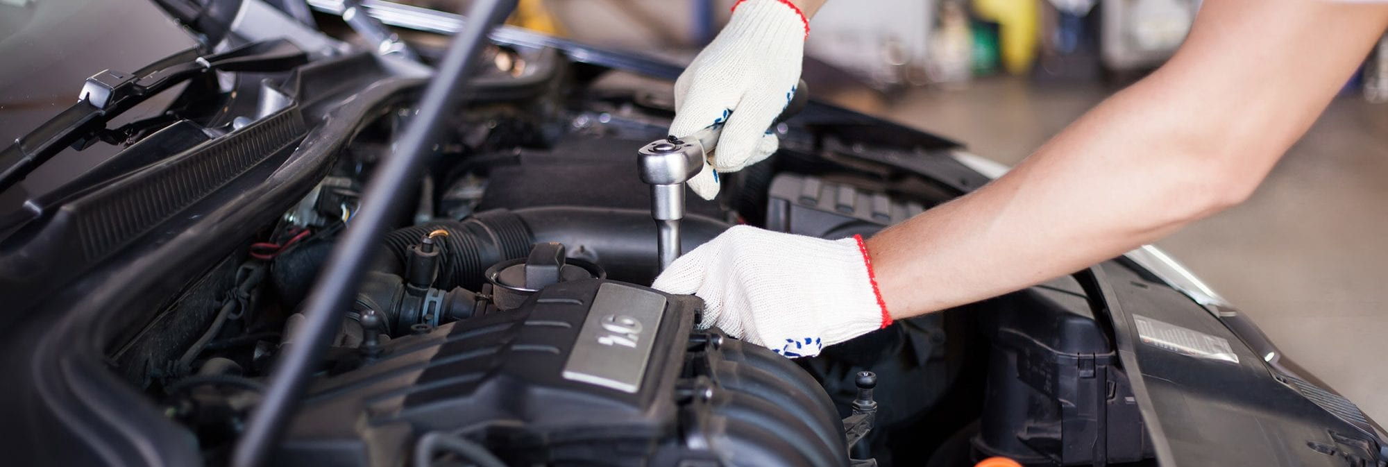 picture of someone fixing a car under the hood
