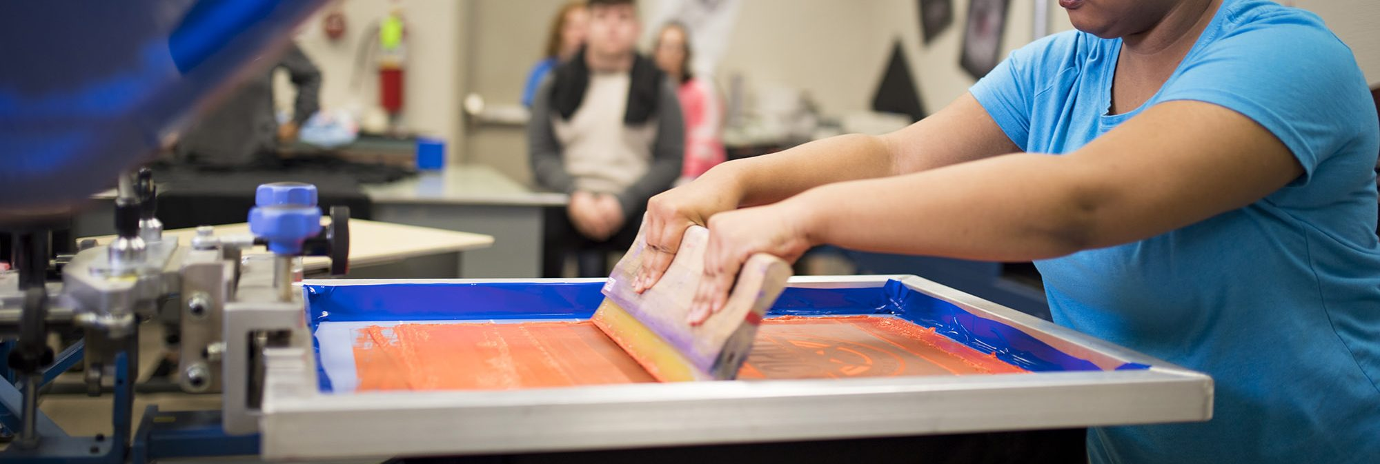 picture of teenager screen printing a t shirt at school