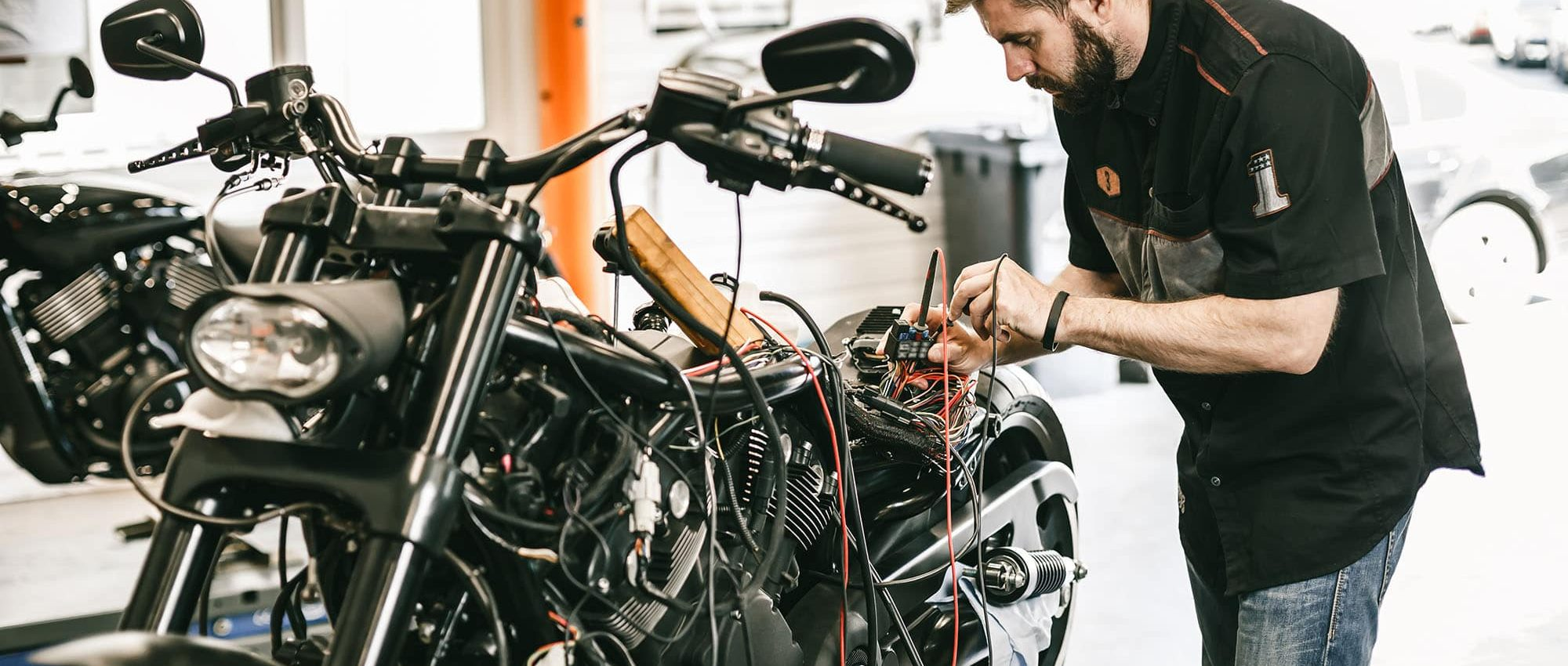 picture of a man fixing a motorcycle in a garage