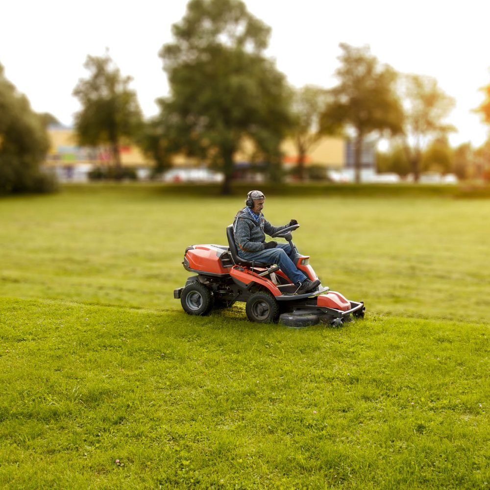 photo of a man driving a lawn mower