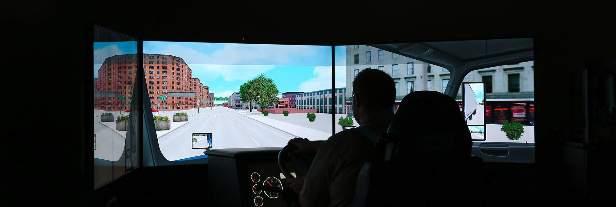 picture of a man in a truck driver training simulator