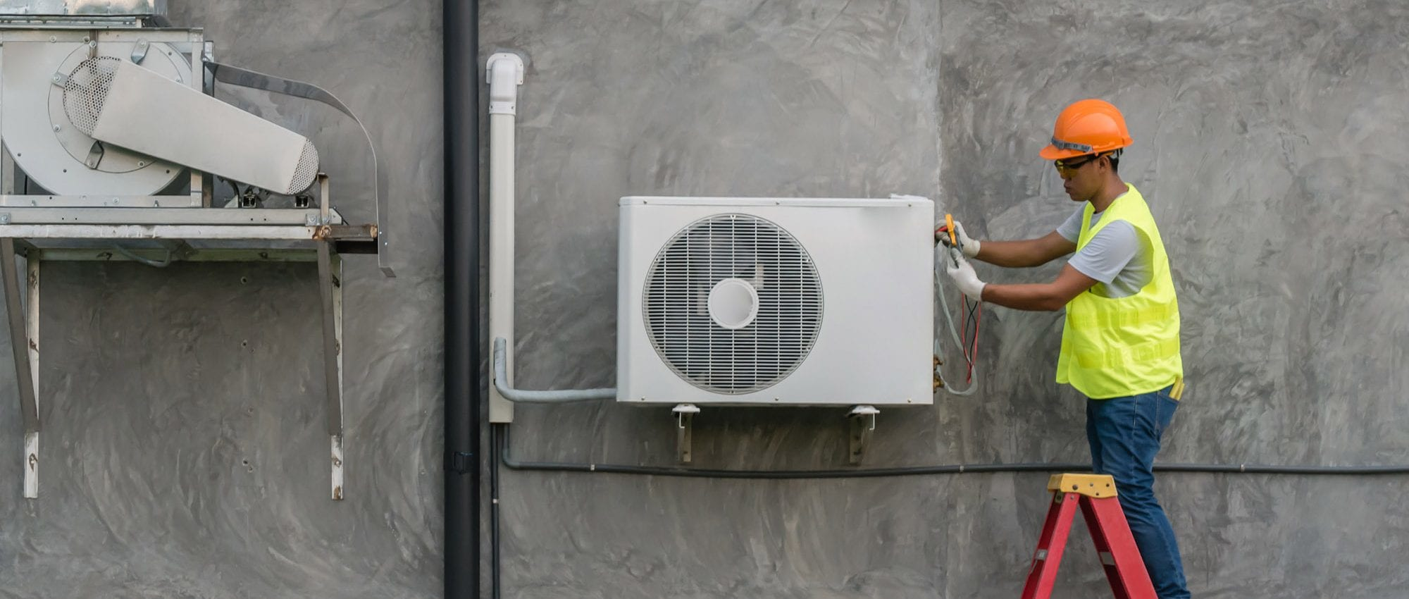 picture of an HVAC Technician checking an AC unit outside