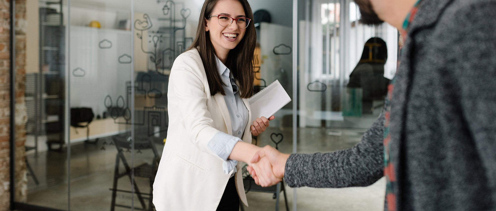 photo of a woman shaking a mans hand at a job interview