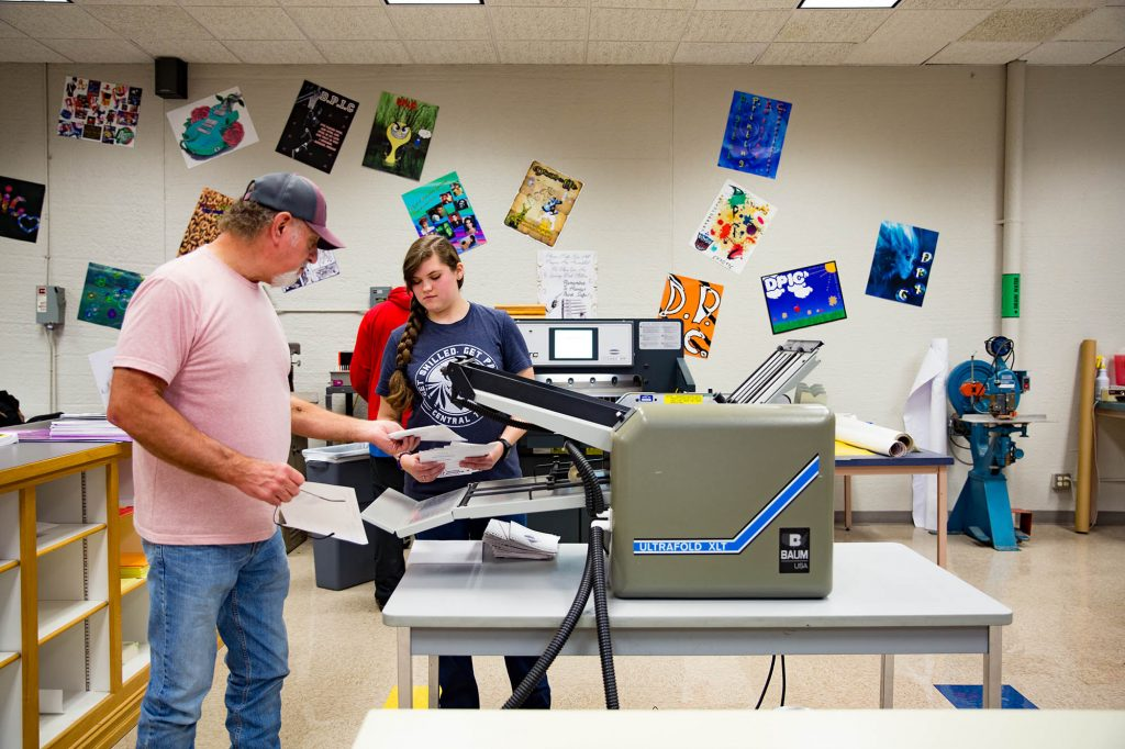 digital printing teacher at Central Tech showing a student how to cut paper
